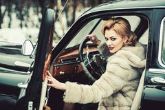 Escort and security guard for luxury woman. sexy woman in fur coat. Travel and business trip or hitch hiking. Call girl. In vintage car. Retro collection car stock photography