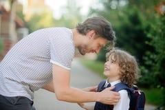 Escortes de père à l'école, fils de premier-niveleuse Image libre de droits