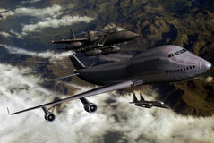 Escorting planes. Two F15 escorting a Boeing 747 over mountains and clouds Stock Image