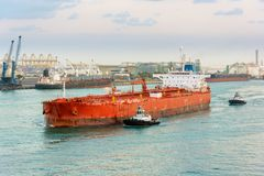 Escorting tanker by tugs. Tug boats towing an empty oil tanker in oil terminal Stock Photos
