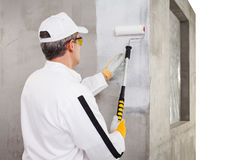 Escorva do trabalhador com um rolo de pintura na parede do cimento Imagem de Stock
