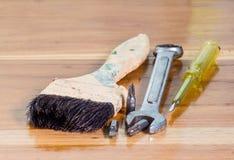 Escova, chaves de fenda e chaves de pintura no fundo de madeira Fotografia de Stock