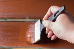 Escova com pintura à disposição Um homem pinta placas azuis em uma escova de pintura marrom Imagem de Stock