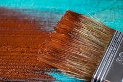 Escova com pintura à disposição Um homem pinta placas azuis em uma escova de pintura marrom Imagens de Stock