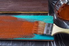 Escova com pintura à disposição Um homem pinta placas azuis em uma escova de pintura marrom Fotos de Stock
