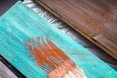 Escova com pintura à disposição Um homem pinta placas azuis em uma escova de pintura marrom Imagens de Stock Royalty Free