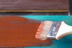 Escova com pintura à disposição Um homem pinta placas azuis em uma escova de pintura marrom Fotografia de Stock