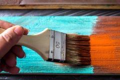 Escova com pintura à disposição Um homem pinta placas azuis em uma escova de pintura marrom Foto de Stock