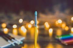 Escova da aquarela e outras fontes da arte com o tiro do bokeh das luzes feericamente na profundidade de campo rasa com tons dour fotos de stock royalty free