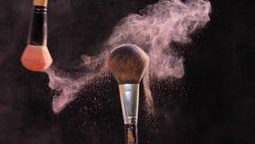 Escova da composição dois com pó cor-de-rosa no fundo preto filme