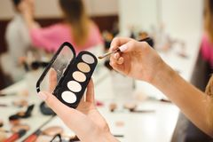 Escova da composição, produtos nas mãos, foto do close up fotografia de stock