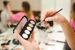 Escova da composição, produtos nas mãos, foto do close up imagens de stock