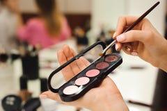 Escova da composição, produtos nas mãos, foto do close up imagem de stock royalty free