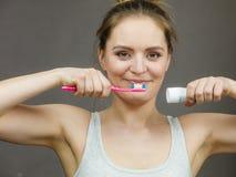 Escova da terra arrendada da mulher e pasta de dente Fotografia de Stock