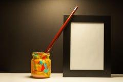 Escova das fontes da arte e quadro preto na luz dramática com fundo preto Fotografia de Stock Royalty Free