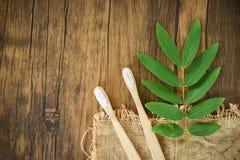 Escova de dentes de bambu e folha verde no fundo rústico - zero banheiros do desperdício para usar o conceito menos plástico foto de stock royalty free