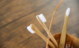 Escova de dentes de bambu em artigos livres plásticos naturais do eco da cesta no fundo rústico - zero banheiros do desperdício p foto de stock royalty free
