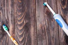 Escova de dentes elétrica em um fundo de madeira preto Fotos de Stock