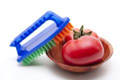 Escova de lavagem com tomate imagens de stock royalty free