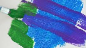 Escova de pintura ascendente próxima que colore uma pintura com cor verde video estoque
