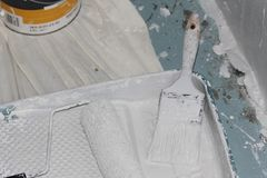 Escova de pintura, rolo de pintura, e bandeja da pintura coberta na pintura branca Fotografia de Stock