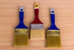 Escova de pintura três na tabela Imagem de Stock