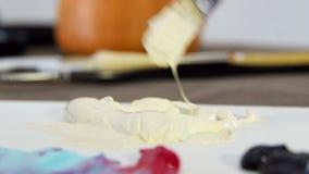 A escova do artista mistura a pintura do marfim na paleta para misturar cores Prepara??o tirar vídeos de arquivo