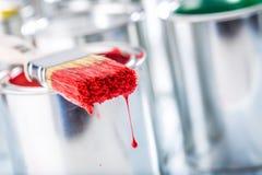 Escova do close-up com a cor vermelha que encontra-se na lata da pintura fotografia de stock royalty free
