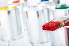 Escova do close-up com a cor vermelha que encontra-se na lata da pintura fotografia de stock