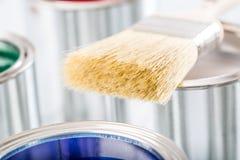 Escova do close-up que encontra-se em latas coloridos da pintura imagens de stock royalty free