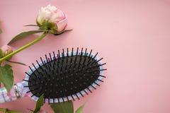Escova do pente da massagem do cabelo com as flores da pe?nia no fundo pastel cor-de-rosa do espa?o da c?pia Configura??o do plan imagens de stock