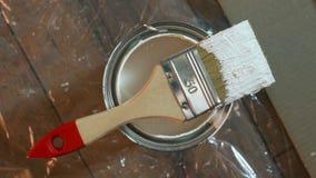 A escova do pintor e a pintura branca estanham o macro sobre o fundo de madeira do teste padrão filme
