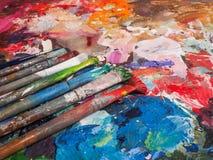 Escova e paleta brilhante da óleo-pintura para o fundo Imagens de Stock Royalty Free