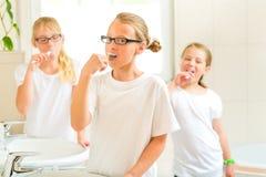 Escovadela de dente das meninas na sala do banho Fotos de Stock Royalty Free