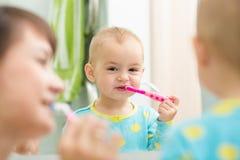 Escovadela de dentes da criança do ensino da mãe fotografia de stock royalty free