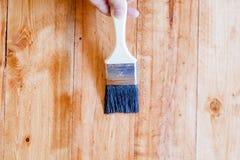 Escovar para aplicar o verniz pinta em uma superfície de madeira Foto de Stock