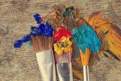 Escovas artísticas em uma pintura colorida pronta para o trabalho Fotos de Stock Royalty Free