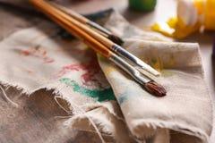 Escovas com pinturas no pano fotos de stock