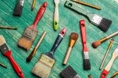 Escovas da composição com as escovas de pintura no fundo de madeira Configuração lisa Imagem de Stock Royalty Free