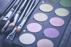 Escovas da composição e sombras para os olhos da composição na mesa Foto de Stock