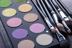 Escovas da composição e sombras para os olhos da composição na mesa Imagens de Stock