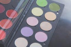 Escovas da composição e sombras para os olhos da composição na mesa Imagem de Stock Royalty Free