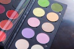 Escovas da composição e sombras para os olhos da composição na mesa Imagem de Stock