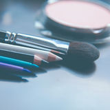 Escovas da composição e sombras para os olhos da composição na mesa Fotografia de Stock Royalty Free