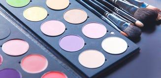Escovas da composição e sombras para os olhos da composição na mesa Foto de Stock Royalty Free