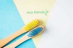 Escovas de dentes de bambu amarelas e azuis Conceito Eco-amigável Fundo mínimo, geométrico Vista superior, espaço da cópia fotos de stock