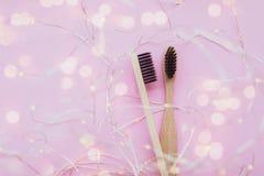 Escovas de dentes de bambu no fundo cor-de-rosa fotos de stock royalty free