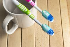 Escovas de dentes no copo branco Fotografia de Stock