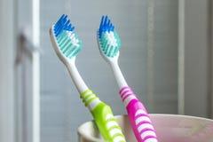 Escovas de dentes no copo branco Fotos de Stock Royalty Free