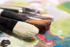 Escovas de pintura artísticas, close-up Escovas usadas do artista que encontram-se em t Imagens de Stock